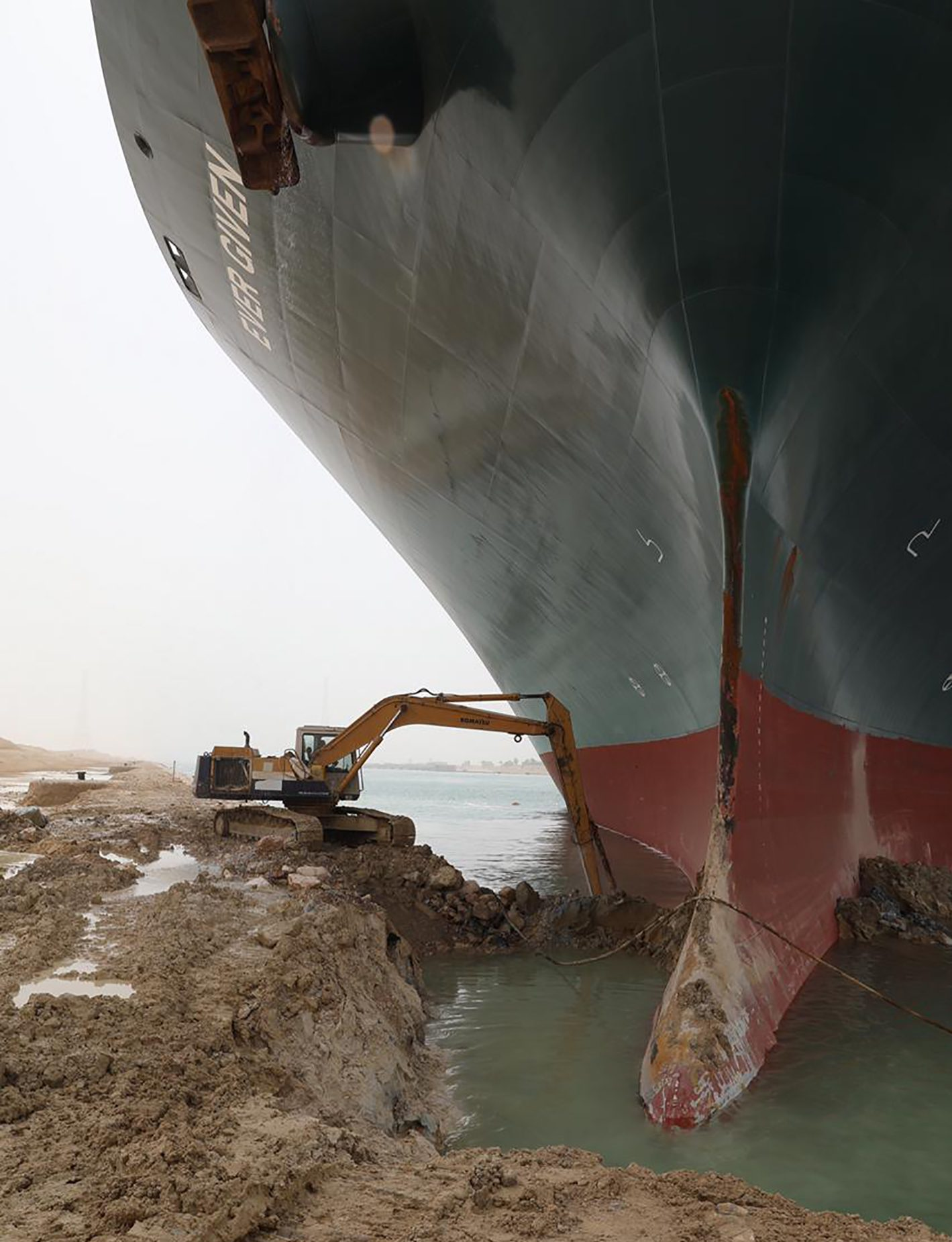 A giant container ship being dug out of the sand